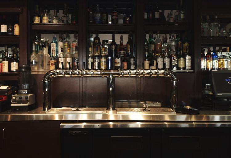 Liquor bottles arranged on bar shelves
