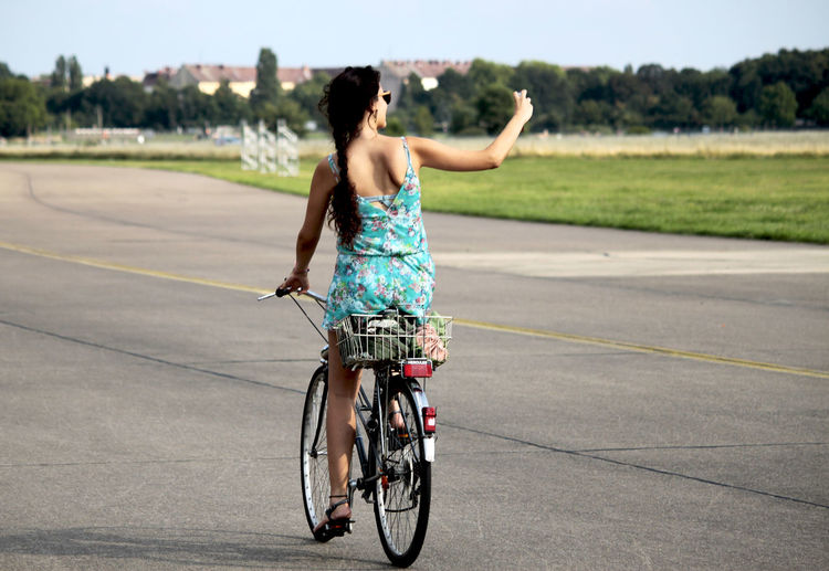 a young woman is riding her bike over the Tempelhofer Feld, Berlin Alone Beauty In Nature Bicycle Bikes Casual Clothing Celebrate Your Ride Confidence  Enjoyment Fahrrad Fashion Fun Lifestyles Motion Real People Selfie Tempelhofer Feld Travel Young Adult