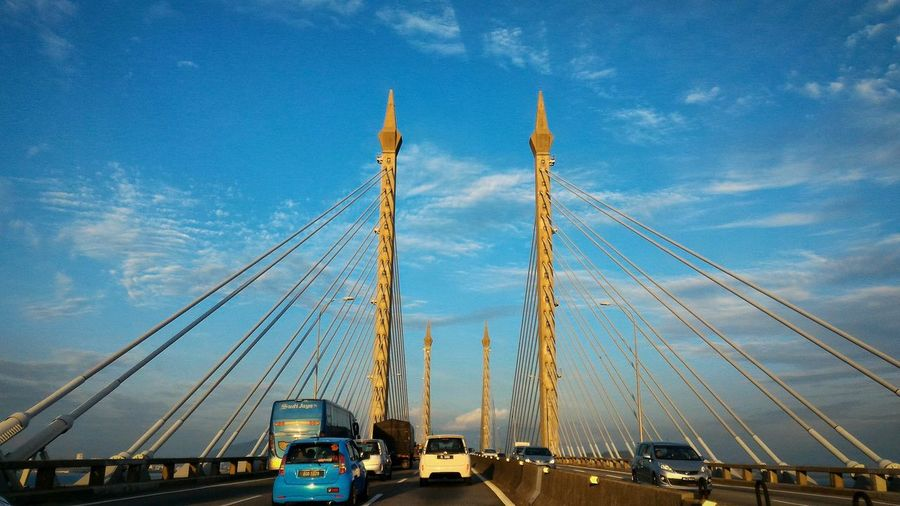 Cars on penang bridge against blue sky during sunny day