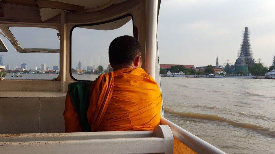 On the way to Wat Arun in Bangkok Bangkok Connected By Travel Architecture Building Exterior Built Structure City Day History Men Monk  Nautical Vessel One Person Outdoors Place Of Worship Real People Rear View Religion Sky Spirituality Standing Tourism Travel Travel Destinations Vacations Watarun Colour Your Horizn