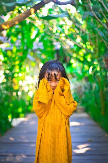 Portrait of cute girl standing on boardwalk against trees