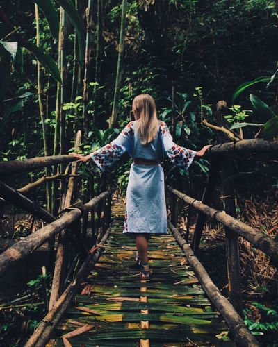 Rear View Of Young Woman Standing On Footbridge In Forest