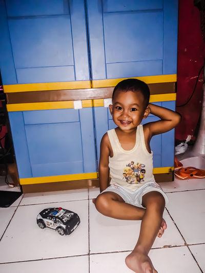 Portrait of smiling boy sitting on tiled floor at home