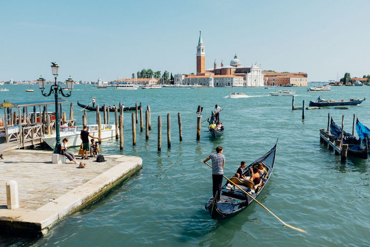 People traveling in boats on sea against church of san giorgio maggiore