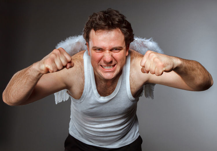 Portrait of man with arms raised against gray background