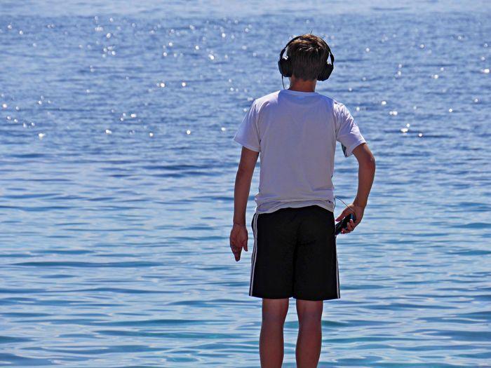 Teenage Boy With Headphones Looking At Water