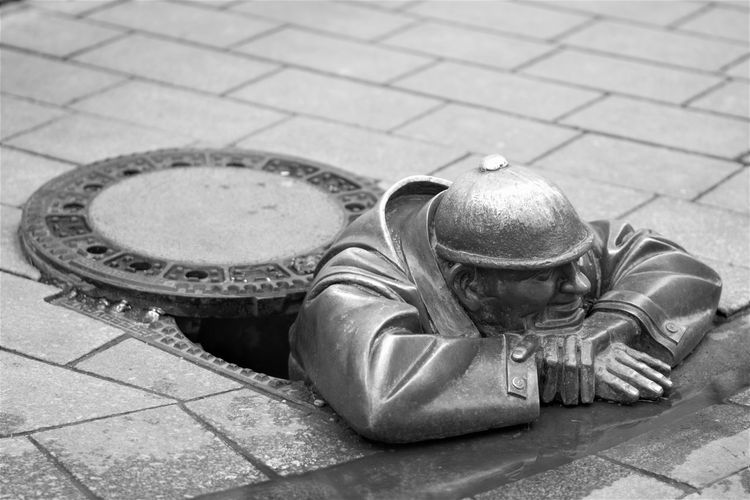 High Angle View Of Bronze Sculpture In Manhole