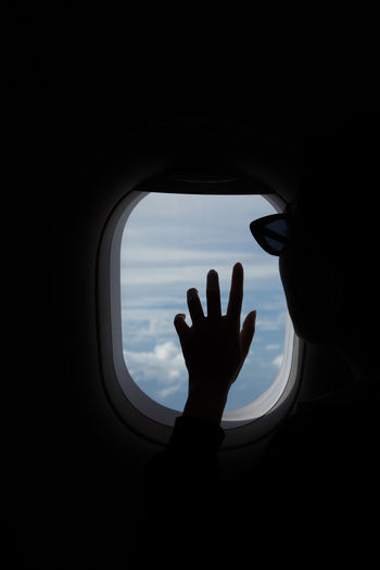 Silhouette of Hand touching window of an airplane. Beautiful Cloud Cloudy Fly Freedom Heaven High Holiday Airplane Airplane Window Beauty Blue Blue Sky Clouds Feline Flight Girl Hand Jet Journey Lifestyles Sky Transportation Travel Window
