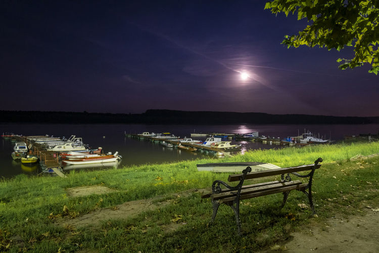 Empty bench on grass by lake against sky at night