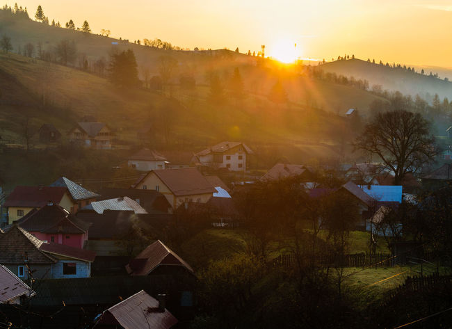 Sunrise over a small mountain village in northern Romania, Bucovina Building Building Exterior Built Structure High Angle View House Lens Flare Nature No People Outdoors Plant Residential District Roof Rural Scene Sky Sun Sunbeam Sunlight Sunrise Town TOWNSCAPE Tree Village Life Capture Tomorrow