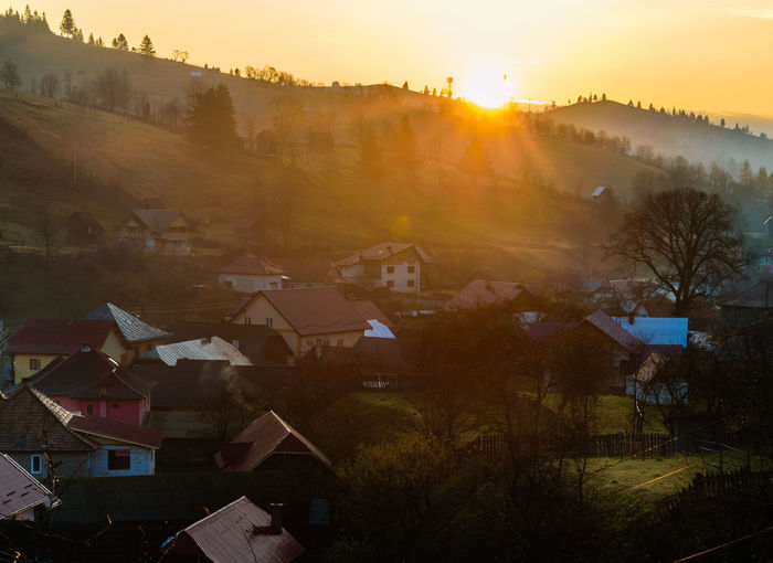 Sunrise over a small mountain village in northern Romania, Bucovina Building Building Exterior Built Structure High Angle View House Lens Flare Nature No People Outdoors Plant Residential District Roof Rural Scene Sky Sun Sunbeam Sunlight Sunrise Town TOWNSCAPE Tree Village Life