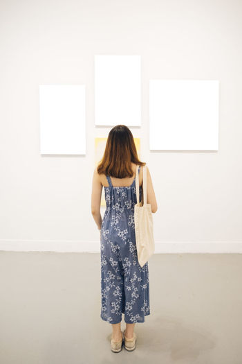 Rear view of woman standing against wall at museum