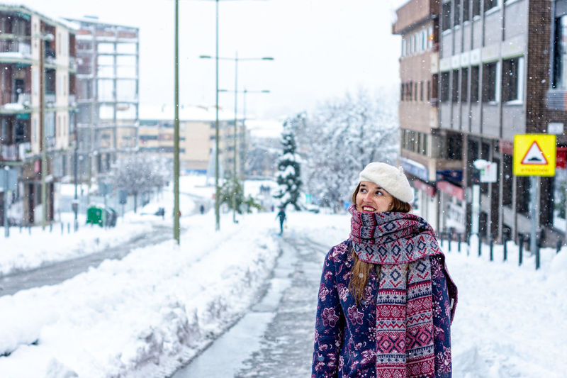 Portrait of woman on snow covered city in winter