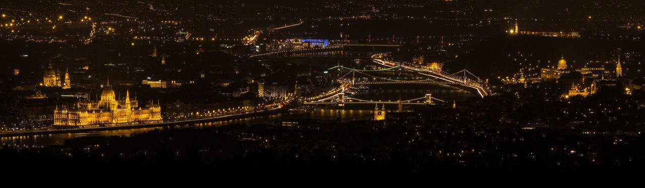Panoramic view of illuminated parliament building and bridge at night