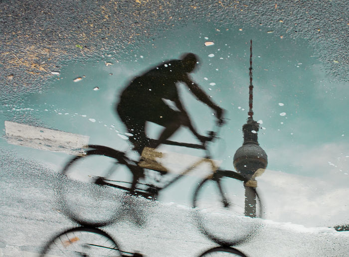 Reflection Of Man Riding Bicycle With Fernsehturm In Puddle On Street
