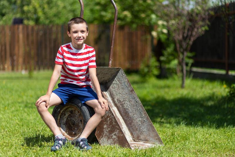 Full length of smiling boy sitting on grass