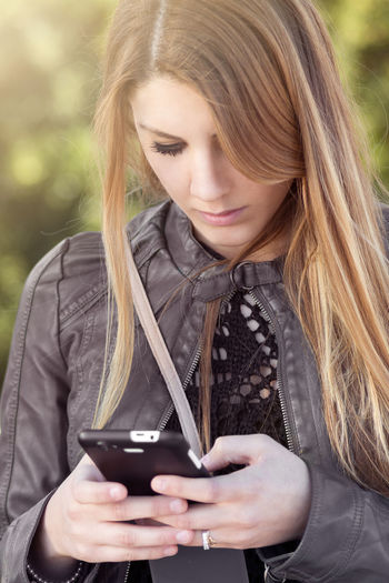 Portrait of beautiful woman using smart phone at outdoors. Beautiful Woman Beauty Blond Hair Casual Clothing Close-up Day Drink Focus On Foreground Food And Drink Front View Headshot Holding Leisure Activity Long Hair One Person One Woman Only One Young Woman Only Outdoors Portrait Real People Refreshment Tea - Hot Drink Women Young Adult Young Women