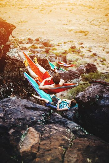 A group of young friends laying out in hammocks attached to a cliff on the mountains while watching a sunset Beach Water Nautical Vessel Sea Sand Outdoors Day Childhood Vacations One Person Nature Children Only One Boy Only People Lifestyle Photography Mountain Range Hammock Time Hammock