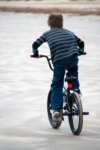 Rear view of boy riding bicycle on snow