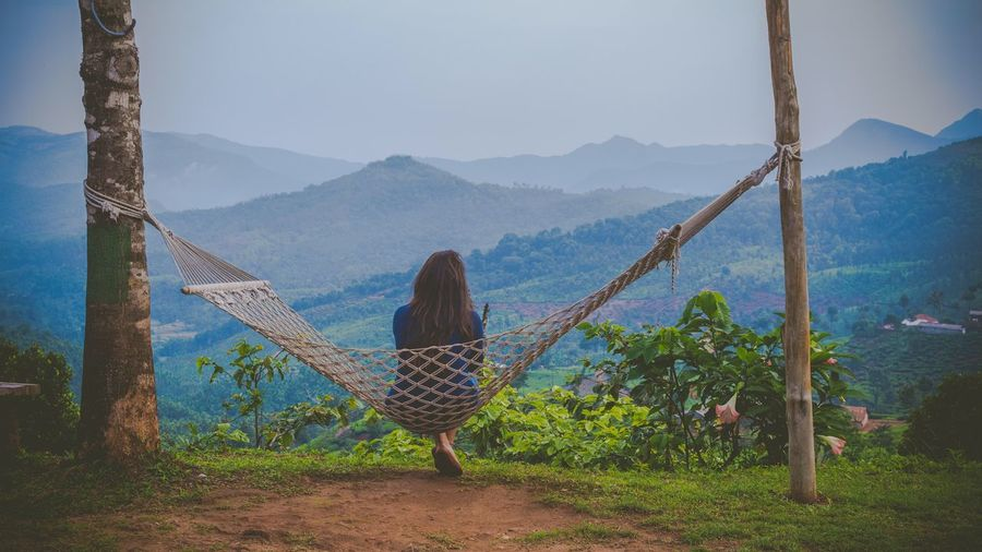 Rear view of woman looking at mountains while sitting on hammock