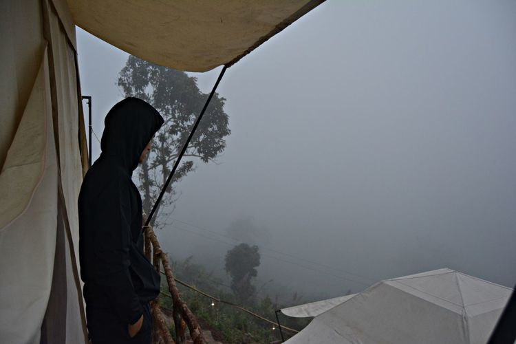 Side view of man standing by tent during foggy weather against sky