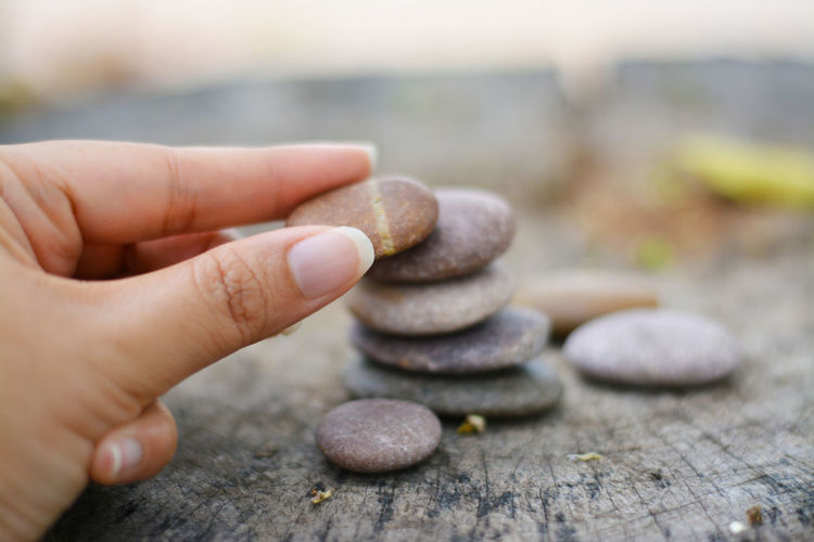 Close-up of person hand holding pebbles