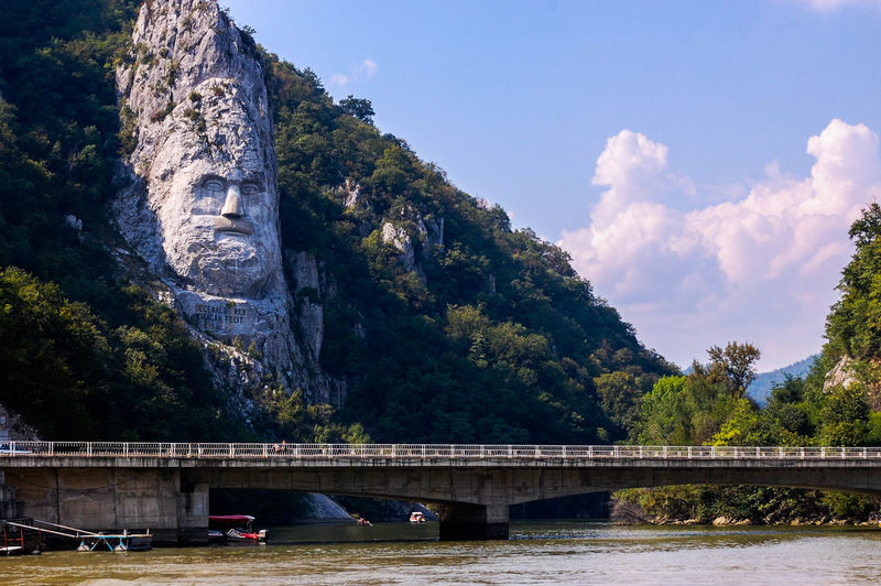 Decebalus carved on rock formation by river against sky