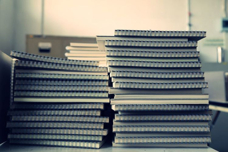 Stack of spiral notebooks on table