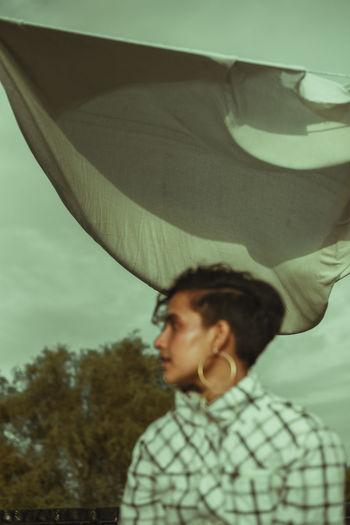 Portrait of boy looking down against sky