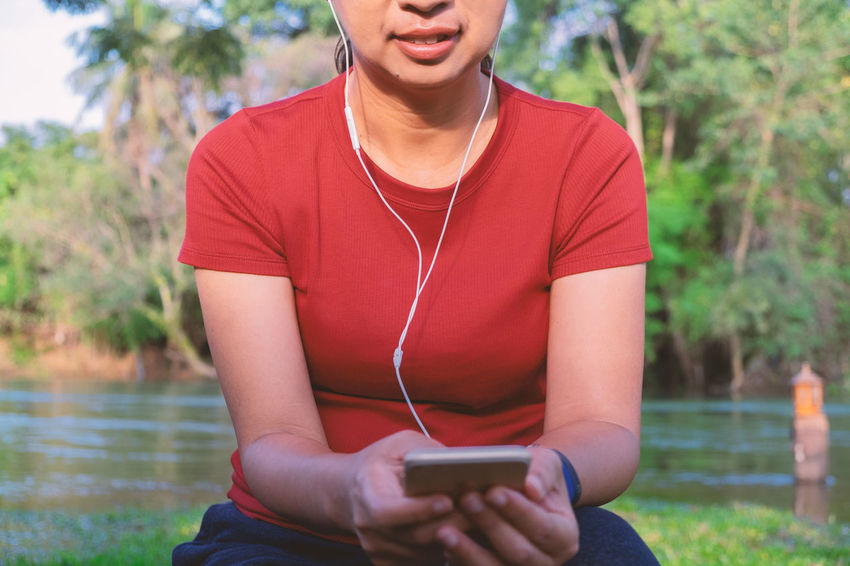 Technology Communication Connection Leisure Activity Portable Information Device Mobile Phone Music One Person Front View Real People Sitting Lifestyles Casual Clothing Smart Phone Headphones Listening Day Holding Nature Outdoors Happiness Riverside River Vacations Hide Away