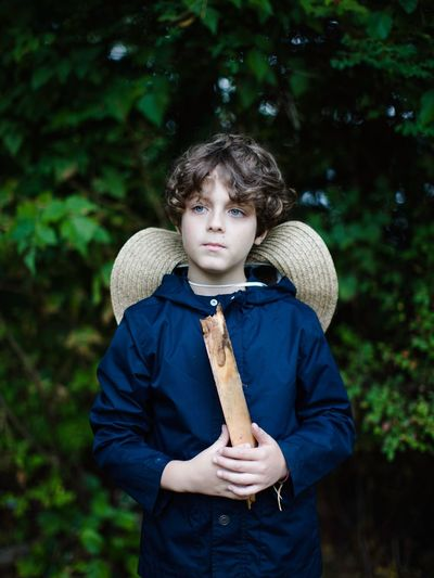 Thoughtful boy holding stick while standing against trees