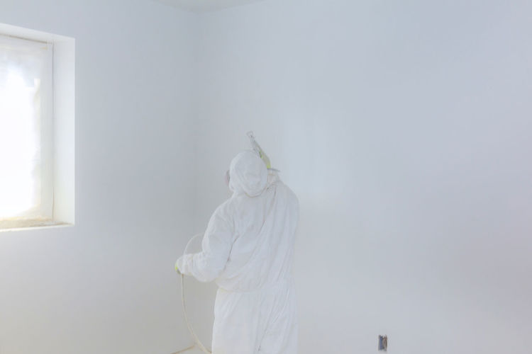 Worker painting wall with Airless Spray Gun in white color. Construction, Repairs Architecture Art And Craft Belief Construction, Building, Structure, Erection, Burrow, Den Copy Space Craft Creativity Day Female Likeness Human Representation Indoors  Male Likeness No People Renovation, Representation Sculpture Spray Paint Spray Paint The Walls Spray Painted Wall Standing Statue White Color Worker, Laborer, Artisan, Worker, Bricklayer, Tiler, Laying Tiles, Floor, Exterior, Feature, Slope,