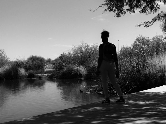 woman and the view Calm Cloud Day Escapism Footpath Full Length In Front Of Lake Men Nature Outdoors Rear View Remote Sky Solitude Standing Tranquil Scene Tranquility Tree Water Waterfront