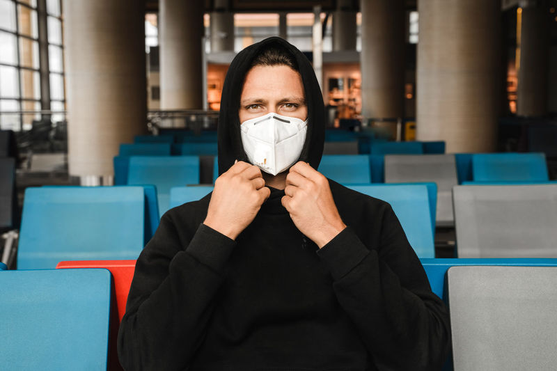 Men in respirator mask n95 sitting at the empty airport terminal. coronavirus covid-19 concept.