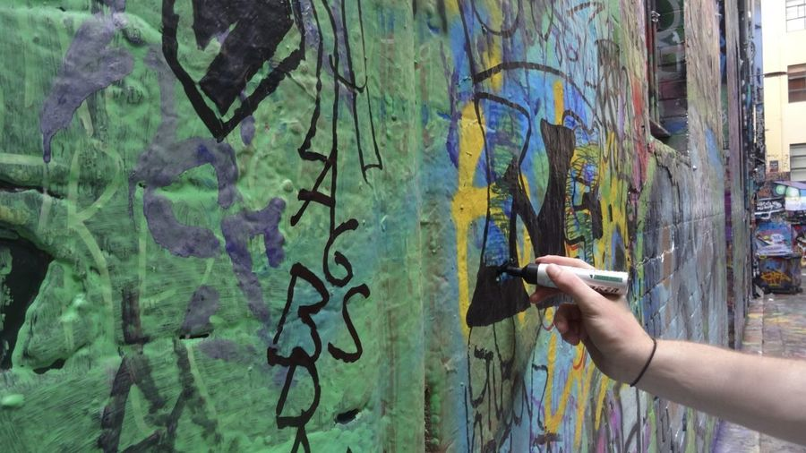 Cropped image of person drawing on graffiti wall