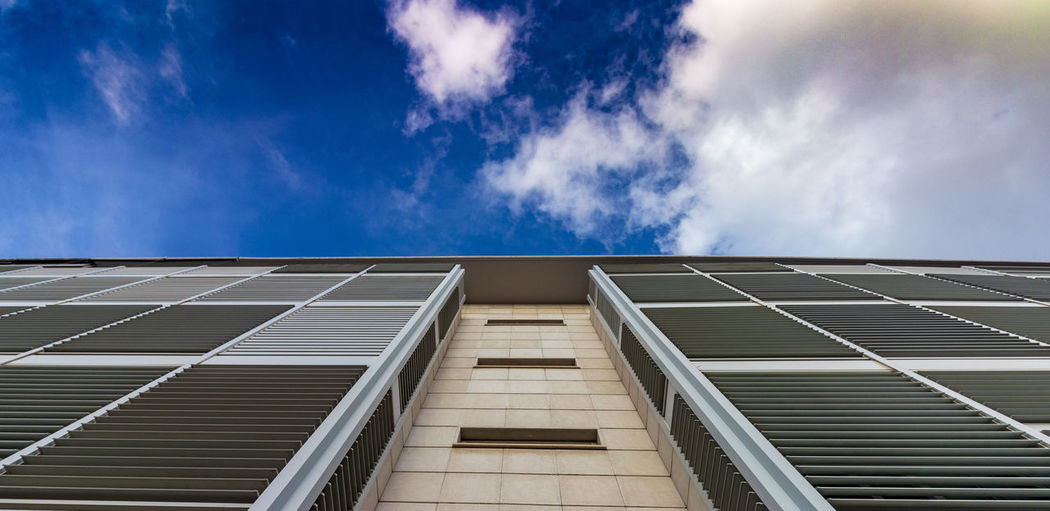 Low angle view of apartment building against blue sky