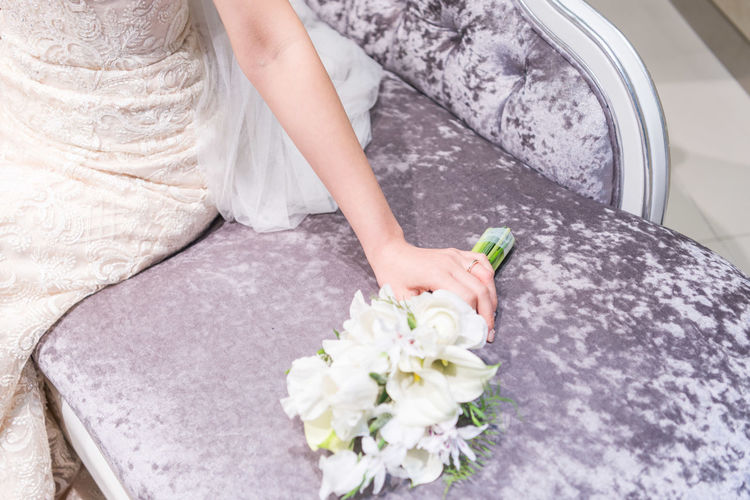 Midsection Of Bride Holding Bouquet While Sitting On Sofa