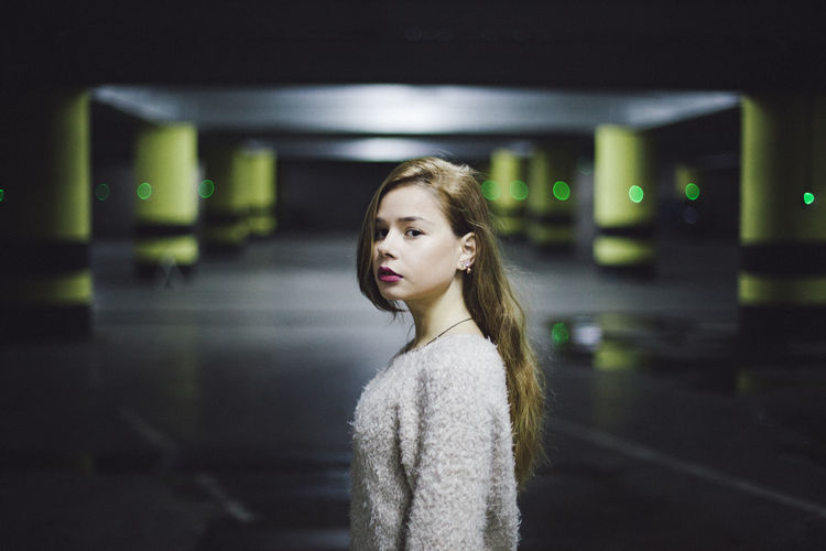 Architecture Beautiful Woman Beauty Casual Clothing Contemplation Focus On Foreground Hairstyle Illuminated Indoors  Lifestyles Night One Person Parking Garage Portrait Real People Standing Waist Up Warm Clothing Women Young Adult Young Women A New Beginning