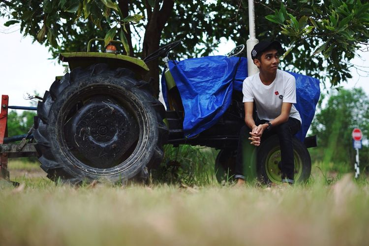 Full Length Grass Transportation Sitting Person Selective Focus Casual Clothing Young Adult Day Mode Of Transport Growth Outdoors Agriculture Nature Rural Scene Green Color Uitmdihatiku Nature Friendship Green Color