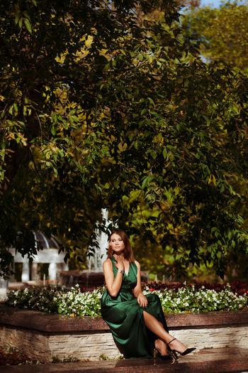 Portrait of sexy woman sitting in autumn park wearing silk green dress