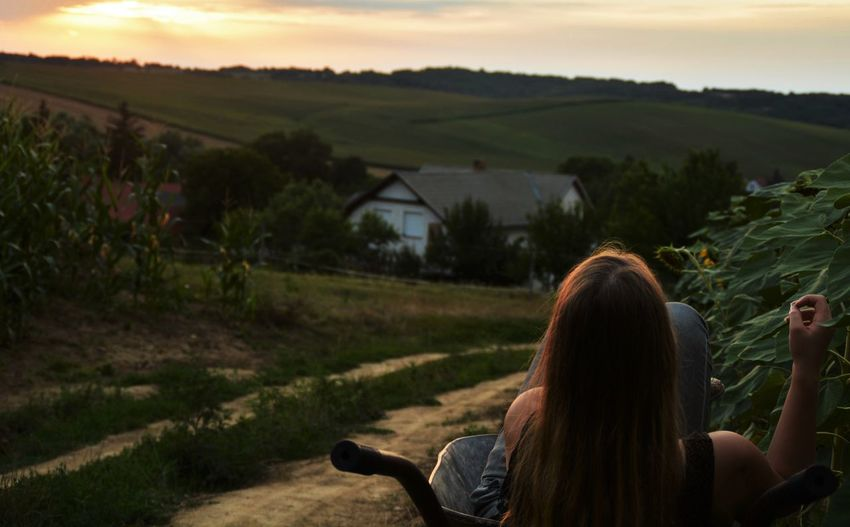 Rear view of woman sitting in wheelbarrow on dirt road against mountain during sunset