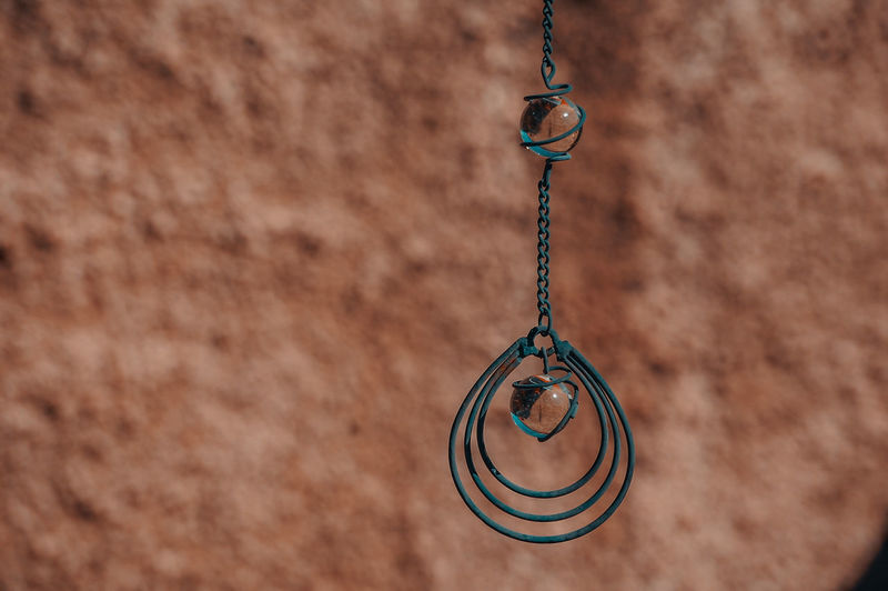 Close-up of pendant hanging against textured wall