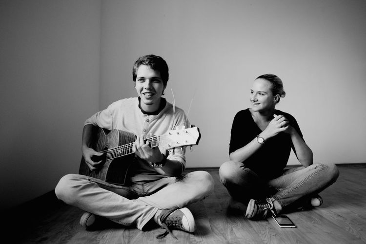 Smiling Young Man Playing Guitar By Friend On Hardwood Floor At Home
