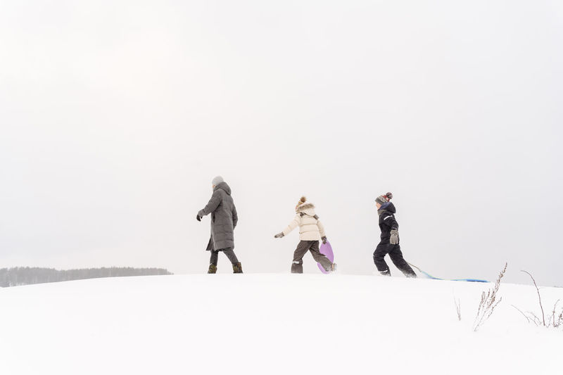 People standing on snow covered field against sky