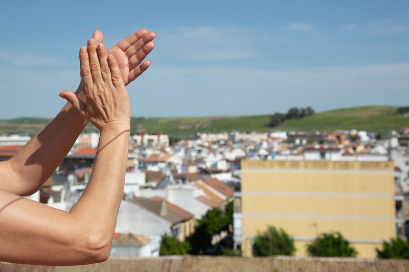Woman hands clapping healthcare staff on balcony