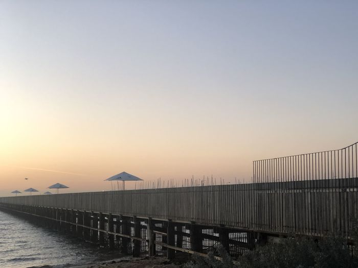 Scenic view of bridge against clear sky during sunset