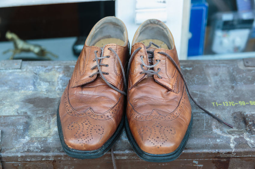 Worn out brogues sitting outside a second hand shop Shoes Brown Leather Used Second Hand Battered Unprocessed No Filter Outside Horizontal No People Brogues Close Up