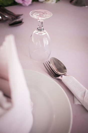 Close-up of plate with spoon and fork on table at restaurant