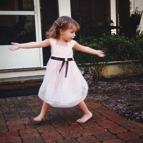 Full length of cute girl dancing in yard