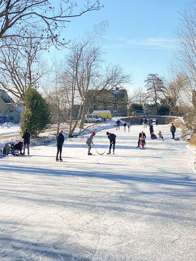 Group of people walking on frozen bare tree